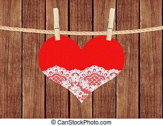 Corazón rojo con encaje colgado de alfileres de ropa sobre fondo de tablones de madera