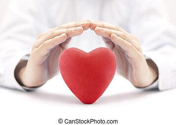 Corazón rojo cubierto de manos. Seguro de salud o concepto de amor