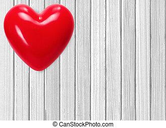 Corazón rojo sobre fondo blanco de madera