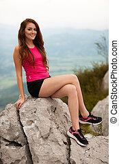 Corredor de mujeres restaura hijo una cima de una montaña sobre el valle