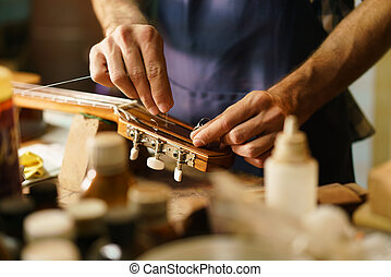 Creador de laúd Artisan arreglando instrumentos de cuerda reemplazando la cuerda de la guitarra
