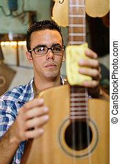 Creador de lute Artisan limpiando instrumentos de música en la tienda