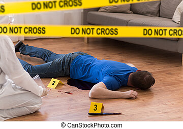 Criminalista recogiendo pruebas en la escena del crimen