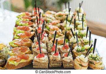 Crostini con diferentes ingredientes en el fondo de madera. Deliciosos aperitivos. Vista frontal. Aperitivos de gourmet: caviar, venado, atún y salmón.