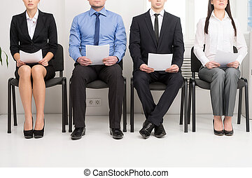 Cuatro candidatos compitiendo por una posición. Tiene CV en la mano