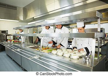 Cuatro chefs trabajando en una gran cocina