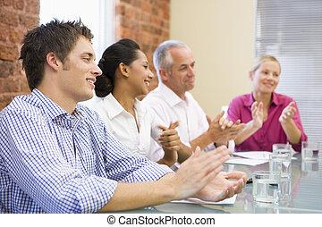 Cuatro empresarios aplaudiendo y sonriendo