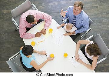 Cuatro empresarios en la sala de juntas con uno sosteniendo un bebé