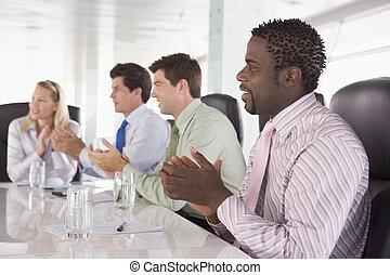 Cuatro empresarios en una sala de juntas aplaudiendo