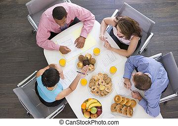 Cuatro hombres de negocios en la mesa con el desayuno