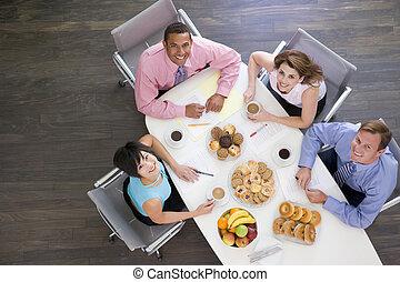 Cuatro hombres de negocios en la mesa con el desayuno sonriendo