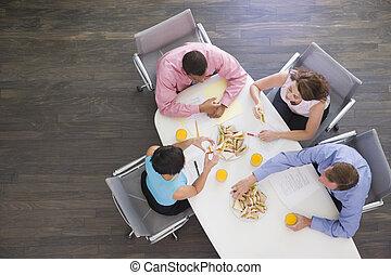 Cuatro hombres de negocios en la mesa de huéspedes con sándwiches