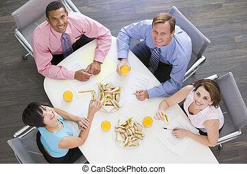 Cuatro hombres de negocios en la mesa de huéspedes con sándwiches sonriendo