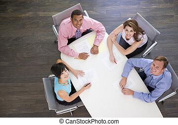 Cuatro hombres de negocios en la mesa de huéspedes sonriendo