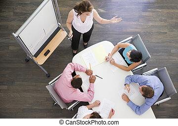 Cuatro hombres de negocios en la mesa de juntas mirando la presentación