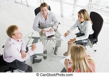 Cuatro hombres de negocios en la sala de juntas con papeleo