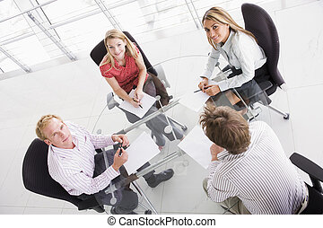 Cuatro hombres de negocios en la sala de juntas con papeleo sonriendo
