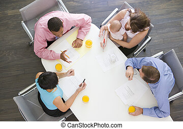 Cuatro hombres de negocios en la sala de juntas con uno sosteniendo un bebé