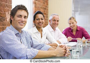 Cuatro hombres de negocios en la sala de juntas sonriendo