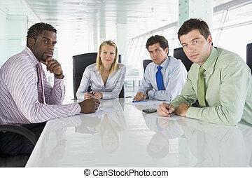 Cuatro hombres de negocios en una sala de juntas
