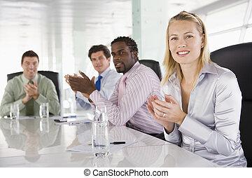 Cuatro hombres de negocios en una sala de juntas aplaudiendo
