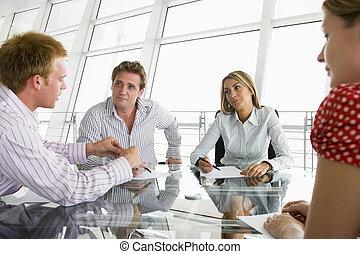 Cuatro hombres de negocios en una sala de juntas con papeleo