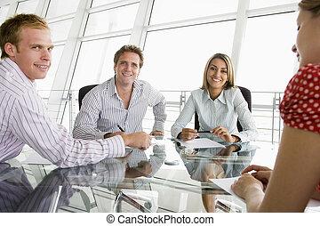 Cuatro hombres de negocios en una sala de juntas con papeleo sonriendo