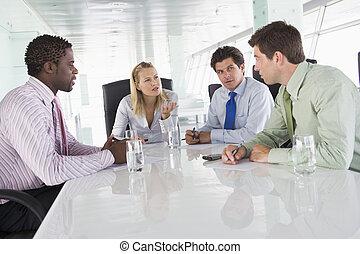 Cuatro hombres de negocios en una sala de juntas hablando