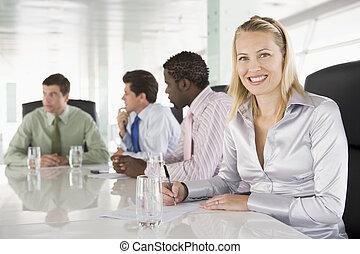 Cuatro hombres de negocios en una sala de juntas sonriendo