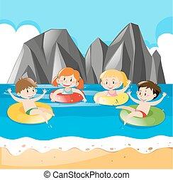Cuatro niños nadando en el océano