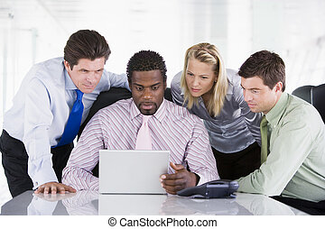 Cuatro personas de negocios en una sala de juntas mirando una laptop