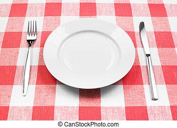 Cuchillo, placa blanca y tenedor en mantel rojo revisado