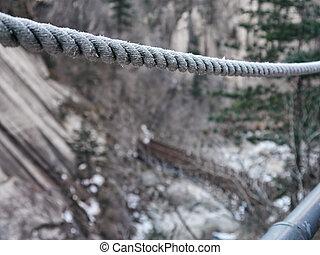 Cuerda en un puente de suspensión en las montañas, primer plano