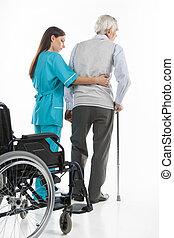 Cuidado mayor. Una enfermera confiada que ayuda a los ancianos a caminar mientras están aislados en blanco