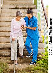Cuidar a la enfermera ayudando al paciente mayor