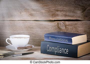 Cumplimiento y regulaciones. Un montón de libros en un escritorio de madera