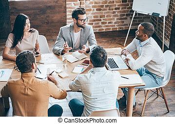 Dar algunos consejos a los compañeros de trabajo. La mejor vista de los jóvenes empresarios discutiendo algo mientras están sentados juntos en la oficina