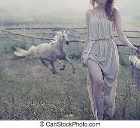 Delicada morena posando con caballo en el fondo
