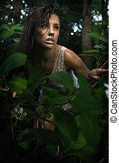 Delicada morena posando en un bosque