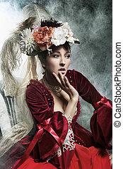 Delicada morena posando en un vestido antiguo