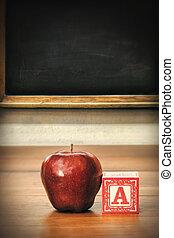 Deliciosa manzana roja en el escritorio de la escuela