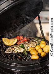 Delicioso pescado de trucha arcoíris con tomates, papas y limón cocinado en parrilla ardiente. Barbacoa. Restaurante