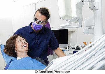Dentista examinando paciente femenina feliz en la clínica