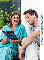Dentista mostrando radiografías al paciente en la clínica