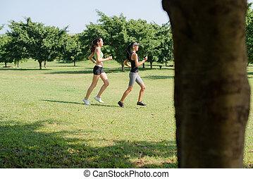 Deporte con dos jóvenes corriendo en el parque