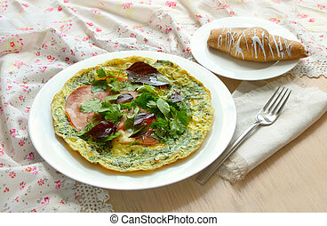 Desayuno con tortilla, jamón, albahaca y croissant.