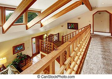 Desde el pasillo hasta el salón al estilo del loft. Rayos de madera en el techo.