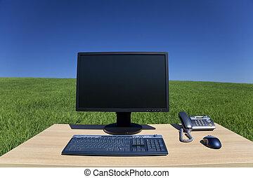 Desk y computadora en campo verde