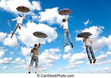 Detrás de cuatro amigos con paraguas en las nubes blancas y peludas en el cielo azul
