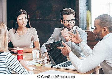 Discutiendo algunos asuntos de negocios. Un grupo de jóvenes discutiendo algo mientras están sentados en la mesa de madera de la oficina